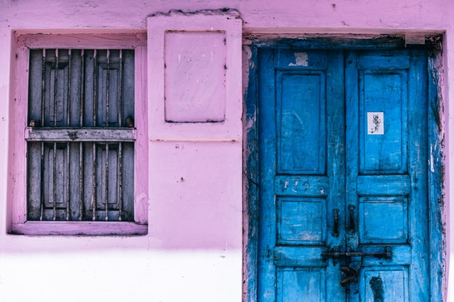 Modré drevené dvere vedľa ružovej steny a dreveného okna