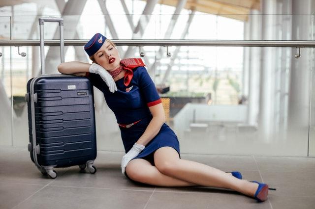 Letuška sedí na zemi a je opretá o cestovný kufor