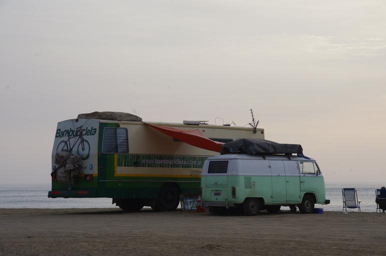 Obytné auto a dodávka zaparkované na brehu mora