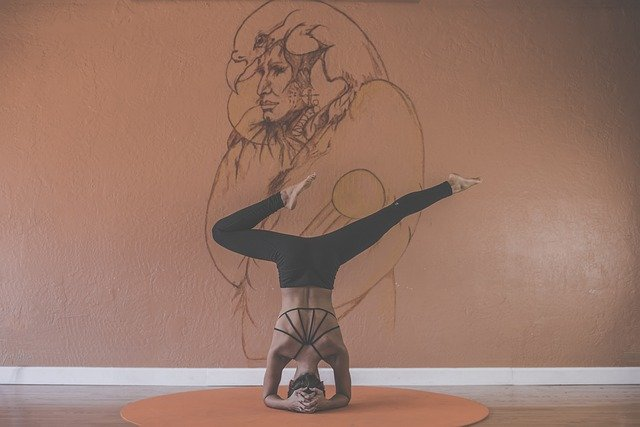 Žena v športovom oblečení stojí na hlave pred oranžovou stenou s kresbou.jpg