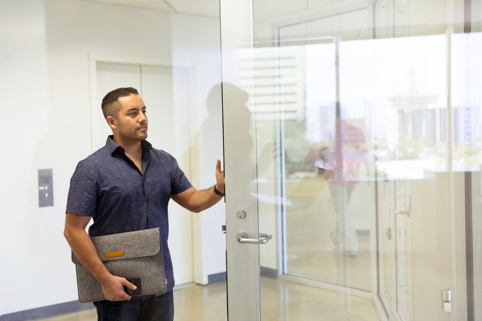 muž pri sklenených dverách